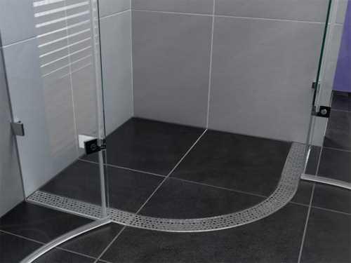 Дизайн малогабаритной ванной комнаты с угловой душевой кабиной без поддона может быть минималистичным. Удачное решение – устроить цельную полосу для слива по контуру стенок кабины
