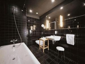 Оформление стен черной плиткой возможно только в просторных комнатах с высокими потолками
