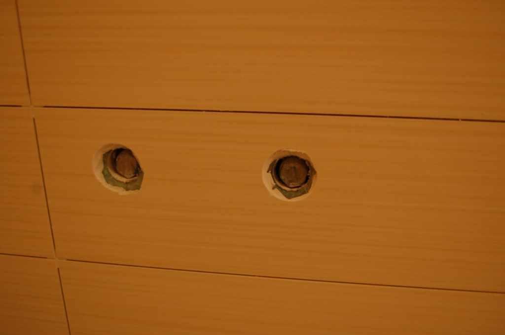 При облицовке, в плитке под эксцентрики можно вырезать отверстия при помощи дрели со специальной коронкой